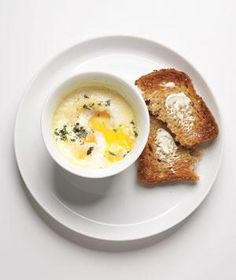 Baked Eggs With Cream and Herbs | Baked eggs are ideal for a low-maintenance breakfast that's also hearty and satisfying. Oftentimes, baked eggs are prepared in bowls with a bit of tomato sauce. To make this version even more versatile, we baked eggs in beds of heavy cream, so, in case they're part of a larger brunch, they work equally well with accompanying dishes that are both savory and sweet. You'll crack eggs into individual ramekins with cream, then bake them in a 425-degree oven for…