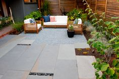 Bluestone paving with pebble accents, crushed granite and cedar fencing work together to transform what was previously an RV parking space into a modern courtyard. The lines of the furniture mimic the lines of the cedar fencing.