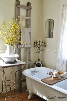 Pretty vintage-style bath... love the claw foot tub & rustic ladder. Adding forsythia to the pitcher/bowl creates a gray/yellow color scheme for spring.