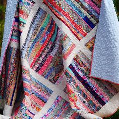 Quilt made with pieces of Liberty lawns that glow set against the white.Q