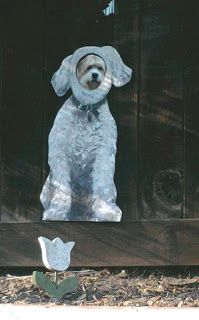 Owners painted photo of their dog and cut out hole from him to look out thru fence, how cute is this?