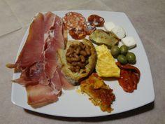 Mixed antipasti: egglpants parmigiana, prosciutto, salame, olives, bruschetta ai fagioli, formaggio fresco, roasted peppers