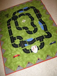 Race Track Quilt -- Bridges/overpasses & car wash that cars can drive thru are stitched into the quilt on one side & attached w/velcro on the other. To store quilt, just release velcro & they lay flat! Snap pockets on binding to store cars!