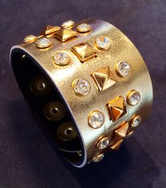 Joxasa gold cuff with pyramid studs.