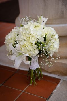 a variety of white blooms are held together with white lace for a simple yet beautiful bridal bouquet - thereddirtbride.com - see more of this wedding here