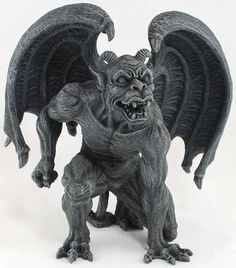 This fierce gargoyle statue stands with a fist cocked back as though he is ready…