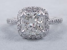 This is our spectacular 2.55 ctw Cushion Cut Diamond Engagement Ring. It has a beauteous 2.02 carat Cushion Cut I Color/VS2 Clarity (Clarity Enhanced) Center Diamond that looks huge and sparkly. It is set in a regal 14K White Gold cathedral setting with petal designs in the basket. Accent diamonds line a halo and travel halfway down the band. This ring is listed for $9,990. Wedding Day, Wedding Rings, Cushion Cut Diamonds, Bling Bling, Clarity, Halo, Bracelet Watch, Cathedral, White Gold