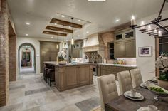 An open-concept kitchen with archways leading into the dining room and a breakfast area to the right. Exposed wood beams in the tray ceiling above the island are a unique architectural detail. Do you like this room? Designed by http://meridithbaer.com/