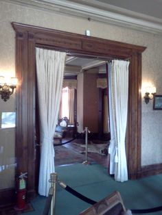 Doorway between Tea Room and formal Drawing Room. All doorways on the first floor of Glenmont have oak pocket doors and swag curtains to create privacy as needed. This doorway is framed by tiger- tail birch in the Tea Room and Rosewood in the Drawing Room.