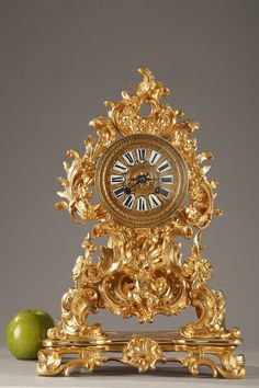 A Napoleon III mantel clock in rocaille style with a rich gilded and chiseled bronze decoration composed of foliate-scrolled, shells, gadrooned leaves, garlands of flowers and acanthuses. In... 3,400€