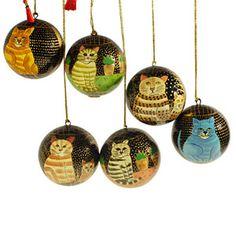 http://www.museesdumonde.com/ext/X096/pid/27668 Boules chats de Noël. Chaque boule est artisanalement peinte à  la main, séchée et vernie d'après les tableaux naïfs de la peintre parisienne Dominique Monat. Une exclusivité de la boutique des Musées du Monde. Des boules de Noël originales en papier mâché laqué livrées avec un fil doré de 20 cm et un pompon rouge. D. 8 cm