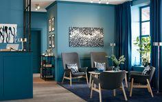 Sala de espera con cuatro sillones de color gris oscuro en la recepción azul de una oficina.