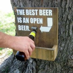 This sign is made of reclaimed wood. This particular sign says THE BEST BEER IS AN OPEN BEER. It has a bottle opener attached, ready to make any beer a good one.