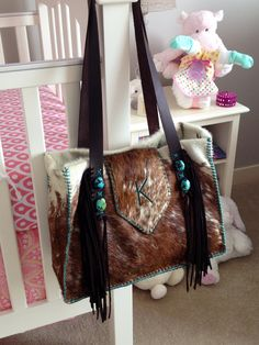 The Buckaroo Diaper Tote. Hair on hide with suede fringe and turquoise. Lined with large interior pockets, key clip and bottle sleeve. gowestdesigns.us