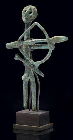 STATUETTE VOTIVE représentant un archer ithyphallique stylisé, filiforme, bandant un arc. Il porte à la taille un glaive. Bronze. Vallée de l'Euphrate, début du IIe millénaire av. J.-C.