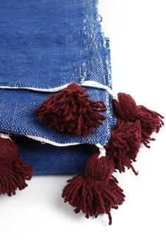 Large Indigo Wool Pom Pom Blanket by Bohemia Design. Working in ethical partnership with traditional Moroccan weavers, Bohemia Design has created a colorful collection of Berber Pom Pom blankets in 100% natural wool and cotton. The blankets are woven entirely by hand on wooden looms and decorated with giant poms poms in classic Berber style. The wools are dyed by the traditional dyers of the Marrakech souks. Handwoven in Morocco.