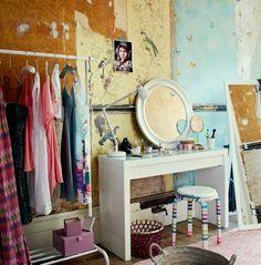 ドレッシングテーブル、ランプ、ミラー、スツール、色とりどりの服を掛けた洋服ラックの画像。壁の一部に古い壁紙が残っている。