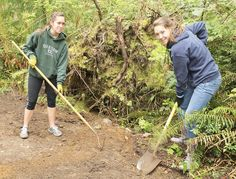 Hannah Long, left, and Jessica Bylin, both seniors at Gig Harbor High School, fill in low spots on the trail to the off-leash dog area on the Bujacich property near McCormick Forest Park. The two helped with Parks Appreciation Day with their school's Interact Club, a service club affiliated with Rotary.
