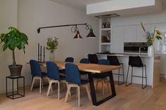 Ruime witte keuken met kookeiland. Daarvoor een tafel om met genoeg mensen te eten. Maar het mooiste is misschien nog wel de lamp!