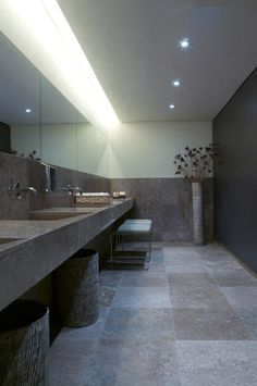Restaurant bathroom. Natural stone + indirect lighting. Calm and luxurious.