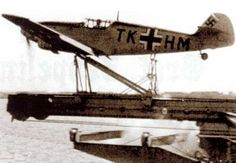 A Messerschmitt Bf-109T is catapulted from a barge during a test, with flaps set for takeoff. It nears the end of the stroke where the cradle will be arrested and the 109 will fly on over the Baltic. Messerschmitt Bf-109T TK-HM is a T-1 variant, without the tail hook as it would be landing at the test facility at E Stelle See (Test Centre Sea) at Travemünde-Priwall. Initial landing and arrestor wire tests were carried out in 1939 using the same aircraft.