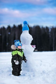 boy in a blue cap next to a snowman in a blue cap