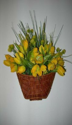 """Baby Yellow Tulips Silk Floral Arrangement in Wicker Wall Basket by N/A. $34.99. Baby Yellow Tulips, Pompoms, and complimenting silk filler, are arranged in a brown wicker wall hanging basket with handle.  A bright and sunny home decor accent for inside or outside.     Approximately 11"""" W x 10""""H"""