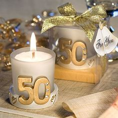 Candle favors measure 2 inches tall by 2 inches in diameter. The candle rests in a whimsical gold base accented with graphic heart designs and number '50' adorned with sparkling rhinestones.
