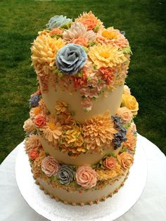 Fall wedding cake that is done up in many sugar paste flowers in fall colors.