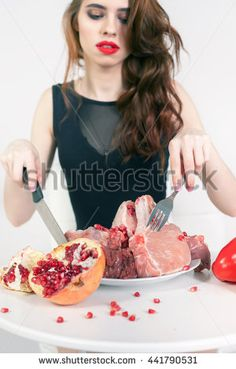 Image of healthy eating. Woman eating flesh meat at restaurant. Cooking meat. There are bell pepper, pomegranate at the table. How to cook?