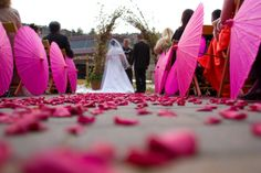 Hot Pink Paper Umbrellas adorn the aisle for an eye popping outdoor wedding