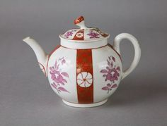 1770 140mm h. Globular teapot with plain spout and handle, with some gilt decoration. Lid has flower knob, green leaves at base of stem. Body of pot and lid are white with four vertical bands of rust-red colour decorated with circular motif and gilt diaper pattern. Mauve flower and leaf spray between bands. Treasurer's House © National Trust / Robert Thrift
