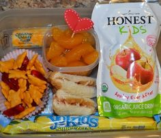 We are rockin' the lunch box today with an Honest Kids Appley Ever After drink, a YoKids Lemonade Squeezer (great frozen, too!), PBJ triangles, Annie's Organic Cheddar Bunnies mixed with Annie's Organic Fruit Snacks, mandarin oranges with a heart topped pick for easy eating, and an Organic Valley String Cheese Snack!  -Lunch created by April from Mama on A green Mission.
