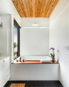 faux plafond bois, baignoire encastrée, carrelage mural blanc neige et fleur décorative