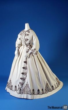 """Medium: White cotton piqué and black cotton cording Date: 1867 Black cording is worked into a stylized variation of the """"Austrian knot"""" on this white piqué afternoon dress. Commonly worn by military officers, the Austrian knot was an applied design of twisted cord or braid used to embellish their uniforms. Here, the interlaced cord work accentuates the skirt's fullness, which is at the back of the dress, and the military motif has been incorporated into a scrolling geometric pattern."""
