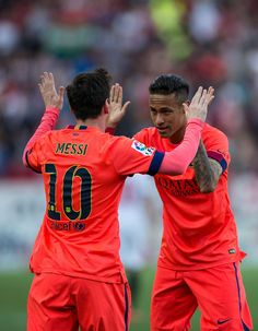 Lionel Messi (L) of FC Barcelona celebrates scoring their opening goal with teammate Neymar JR. (R)during the La Liga match between Sevilla FC and FC Barcelona at Estadio Ramon Sanchez Pizjuan on April 11, 2015 in Seville, Spain.