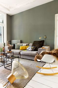 Great color combination: We love the modest green wall of this living room. It's a perfect match to the comfortable grey couch with a bunch of pillows and this neutral carpet. Great eyecatcher: a beautiful lamp in shape of a light bulb and a white RAR rocking armchair with a cozy brown fur.