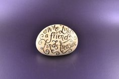 These pebbles are hand-painted with the quotation Who finds a friend finds treasure.  The calligraphy is painted in black acrylic with metallic