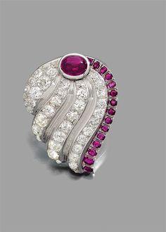 SUZANNE BELPERRON ANNEE 1936 CLIP COQUILLAGE RUBIS Il représente un coquillage stylisé entièrement pavé de diamants taille brillant (TA) et de rubis ovales. Un rubis cabochon plus important en sertissure. Monture en or gris 18K et platine. Travail français, poinçon de maître Groene et Darde. Poids brut : 33,1 gr. Dimensions : 4,8 x 3,8 cm Le clip est accompagné d'un certificat d'authenticité de Monsieur Olivier Baroin.