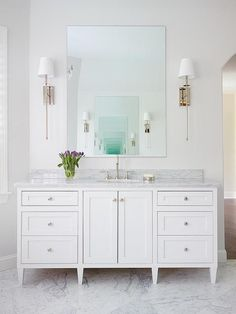 Elegant bathroom features a custom footed white single vanity adorned with nickel knobs topped with marble fitted with an oval sink and gooseneck faucet under a silver framed mirror illuminates by polished nickel long sconces.