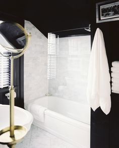 Lonny mag- A black bathroom with marble tile and a brass mirror