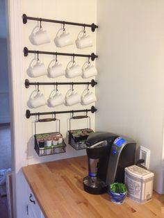 tazas de café colgadas en barras de hierro pegadas a la pared