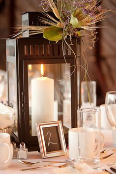 Lantern centerpiece, candle and flower decor to compliment rustic appeal. Silver frame with table number.