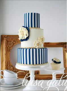 Navy blue, white and gold couture wedding cake with nautical rosettes and stripes