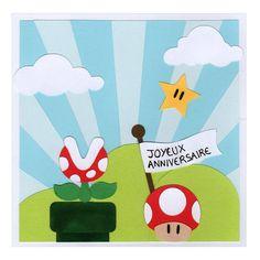 La carte anniversaire pour enfant est une carte double carrée décorée d'éléments inspirés de l'univers Super Mario : le super champignon fait de papier rouge avec des taches en papier...