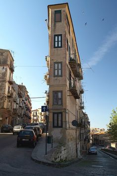 """Thin apartment building in Italy, found via The World Geography - """"Old three-storey building from the picture still has tenants, judging by arranged balconies. This thin structure is probably located in some old neighborhood in the Italian province of Caltanissetta on the island of Sicily."""""""
