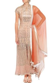 A peach collared straight cut georgette kurta with gota patti leaf motifs all over and mirror work around the hem. It has a front slit in the centre. It comes along with a pair of matching pants in modal fabric with cutdana and thread work triangular motifs around the hem. It also comes along with a peach to coral shaded net dupatta with an ivory border. Shop Now at www.carmaonlineshop.com #carma #carmaonlineshop #designer #online #gotapatti #coral #silk #ivory #embroidery #devnaagri…