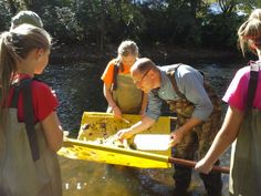 Jeff Bernard, a facilities site manager at GM's Lansing Grand River Assembly plant, and students from St. Thomas Aquinas Parish School retrieve water samples from the Red Cedar River in East Lansing, Mich., during a GM GREEN event in October 2013.