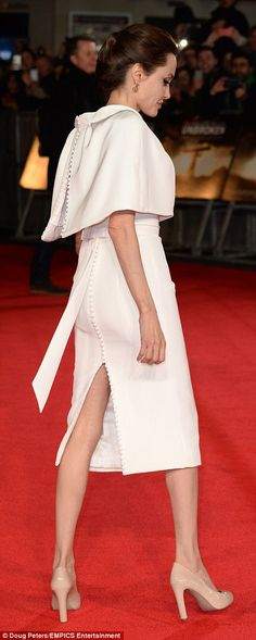 All-white on the night: Angelina stunned in her standout cream gown with a cape neckline, which she teemed with nude heels, and added a Poppy pin by Buckley London