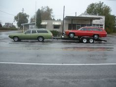 1973 Plymouth Satellite Custom wagon pulling another Satellite Custom on a trailer behind it.